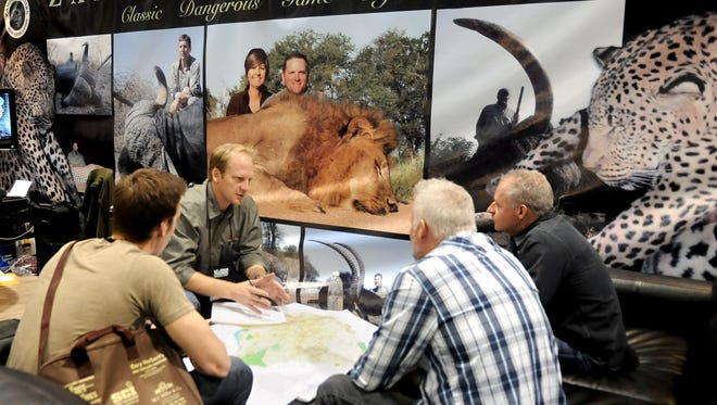 Alistair Pole, second from left, owner of Zambezi Hunters in Zimbabwe, Africa, talks about a safari with Jeff VanDrunen, right, Daniel Cavender and David VanDrunen, back to camera, during the Safari Club International convention in Reno, Nev. on January 24.