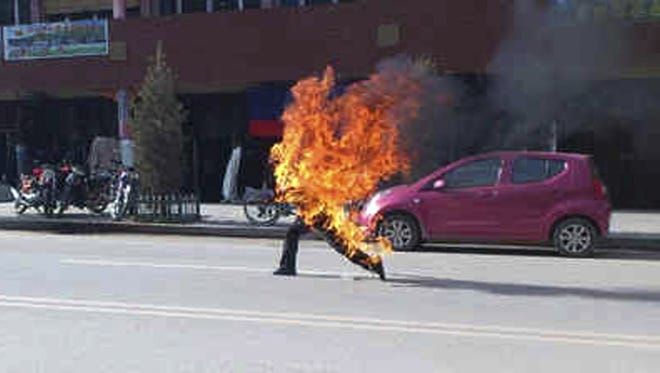 Dorje Rinchen, a farmer in his late 50s, runs after setting himself on fire on the main street in Xiahe, in northwestern China's Gansu province.