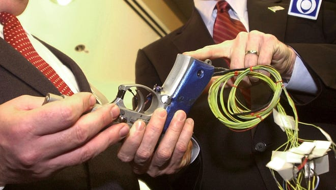 """In this Tuesday, Jan. 6, 2004 file photo, New Jersey Gov. James E. McGreevey, right, points to the handle of a """"smart gun"""" with grip recognition technology, held by the gun's inventor Michael Recce, associate professor of information systems at New Jersey Institute of Technology in Newark, N.J."""