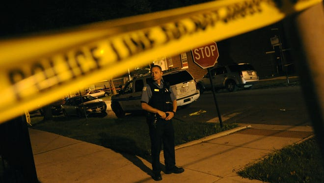 A Chicago police officer guards the perimeter of a crime scene as investigators work the scene of an officer-involved shooting in the North Austin neighborhood on the city's West Side late Sunday, September 9, 2012.