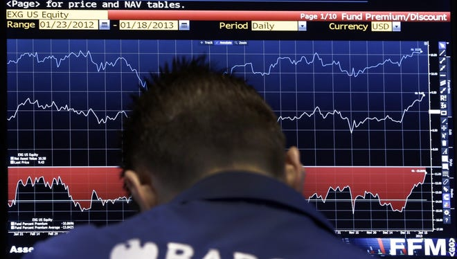 A trader checks a screen at his post on the floor of the New York Stock Exchange.