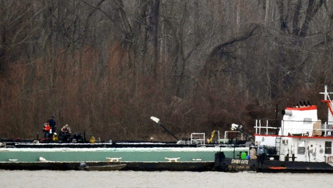 Cleanup crews try Jan. 27 to contain oil leaking into the Mississippi River.