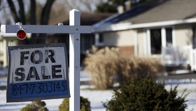 "A ""for sale"" sign hangs outside a home Jan. 5 in Glenview, Ill."