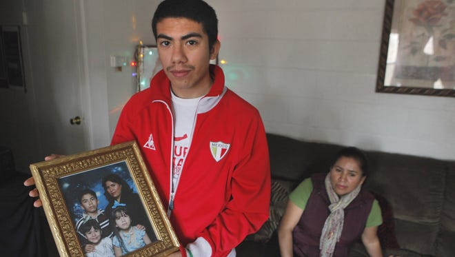 Jose Cabrera, 17, holds a family photo with his two younger sisters who are U.S. citizens. Maria Cabrera, seated, and her son hope that U.S. immigration policy changes would allow a path to citizenship for them and others.