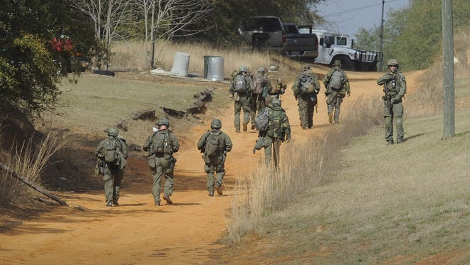 Police officers move towards the home where a standoff continues on January 30.