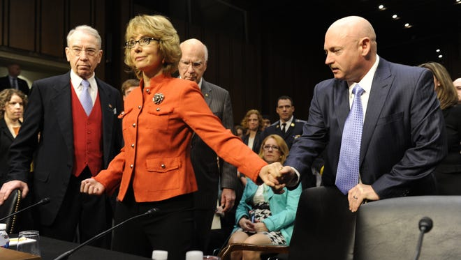 Former Arizona congresswoman Gabrielle Giffords and her husband, Mark Kelly,  prepare to testify. Sens. Chuck Grassley, R-Iowa, left, and Patrick Leahy, D-Vt., greeted them.