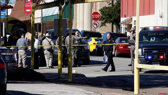 Law enforcement officers investigate the scene of a shooting in downtown Kaufman, Texas on Thursday,  Jan. 31, 2013.  A prosecutor was shot and killed Thursday morning near the Texas courthouse where he worked, and authorities said they were searching for two suspects. Officials didn't immediately indicate any motive. The courthouse was initially locked down, but that has since been lifted, county spokeswoman Pat Laney said. The name of the prosecutor was not immediately announced, pending notification of family. (AP Photo/The Dallas Morning News, David Woo) ORG XMIT: TXDAM102