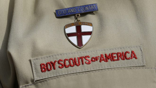 This photo taken  Monday shows a close up detail of a Boy Scout uniform worn by Brad Hankins, a campaign director for Scouts for Equality, as he responds questions during a news conference in front of the Boy Scouts of America headquarters in Irving, Texas.