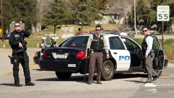Police stand at a road block at Highway 38 and Bryant Street, just north of Yucaipa, Calif., as a gunfight between police and man said to be fugitive ex-Los Angeles cop Christopher Dorner takes place farther up the highway.