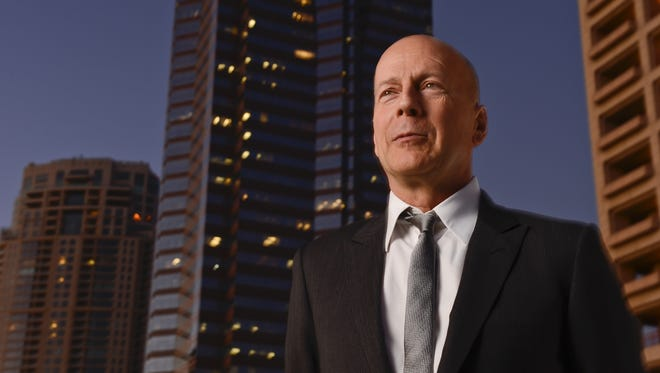 "Bruce Willis with the Nakatomi Plaza building in the background where the main action from the first 'Die Hard' movie took place. ""It all started over here,"" says Willis."