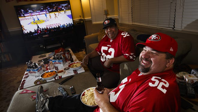 """Kornel Lelea, front, and Tony Jones in Lelea's living room, which has a 70-inch TV. """"With the (new) 70-inch now, it's better than a movie theater,"""" he says."""