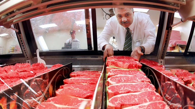 Mike Hoffman, meat manager for Dahl's Foods in Des Moines, Iowa, loads a fresh platter of steaks into the beef case at the Merle Hat Road location on February 7.