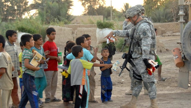 U.S. soldiers from the 30th Heavy Brigade Combat Team, 1st Cavalry Division, pass out toys to local children during a Human Terrain Team site survey mission, in Kilabeen, Iraq, on Sept. 15, 2009.