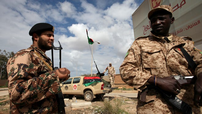 Libyan security forces stands guard in Benghazi, Libya, Saturday.