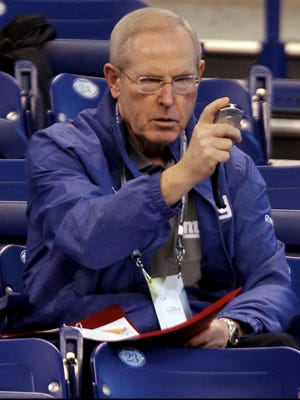New York Giants head coach Tom Coughlin checks his stop watch at the NFL scouting combine in Indianapolis, Monday, Feb. 27, 2012.