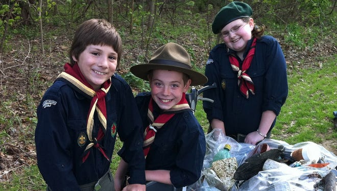 This 2011 photo provided by the Baden-Powell Service Association shows Pathfinder members Noah Kresse, Jude Atchley and Laura Gardner of the 10th Daniel Boone BPSA Scout Group working during an annual service project cleaning up 3 miles of trails along the Missouri River in Washington, Mo.