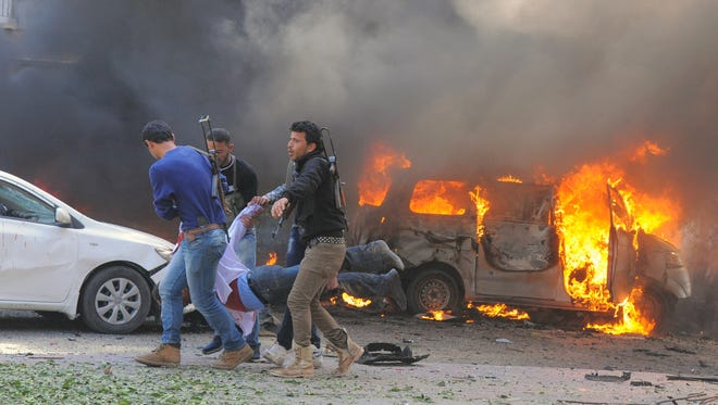 A handout picture released by the official Syrian Arab News Agency (SANA) on Thursday shows Syrians carrying an injured man after a powerful car bomb exploded near the headquarters of Syria's ruling Baath party in the center of Damascus.
