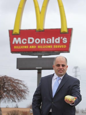 Dearborn attorney Majed Moughni holds what is advertised as a halal chicken sandwich at a Dearborn, Mich. McDonald's on January 31.