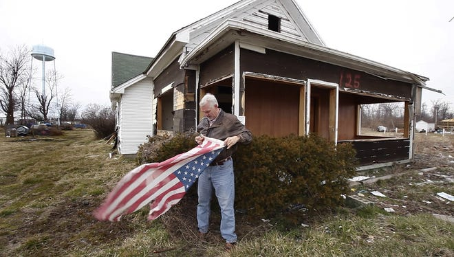 Clark County Commissioner Rick Stephenson stops to fold a tattered American flag on February 21, in front of a Marysville, Ind. house that was damaged by a March 2012 tornado.