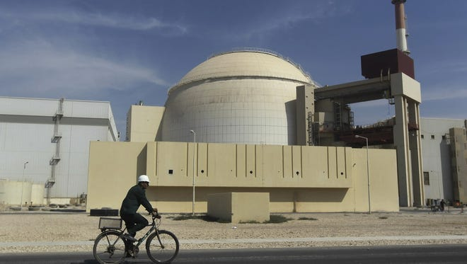 In this Oct. 26, 2010, file photo, a worker rides a bike in front of the reactor building of the Bushehr nuclear power plant, just outside the southern city of Bushehr, Iran.