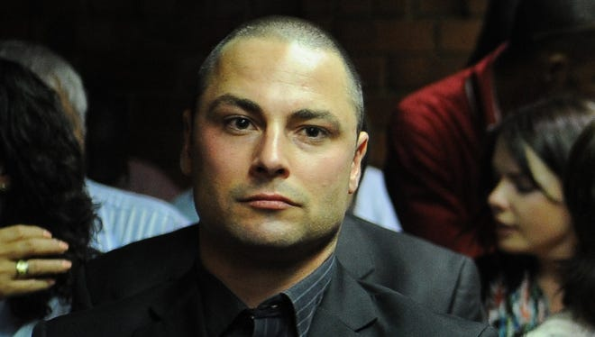 Carl Pistorius watches as his brother, Olympian Oscar Pistorius, appears in South Africa court on Feb. 22. Oscar faces a  premeditated murder charge in the death of his girlfriend.