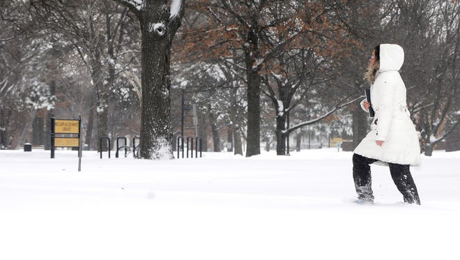 An Emporia State University student walks around campus in the midst of the storm on Feb. 21 in Emporia, Kan.