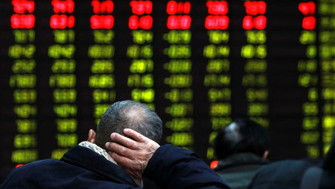 An investor in China supports his head with a hand while looking at an electric stock price display at a trading hall in a securities firm in Shanghai, China.
