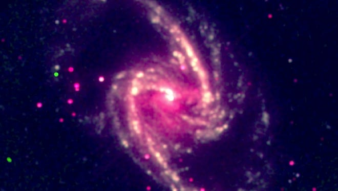 This image released by Arcetri Astrophysical Observatory, shows a supermassive black hole in the nearby spiral galaxy NGC 1365. A study published Thursday in the journal Nature calculated the spin rate of the black hole and found itís rotating close to the speed of light.