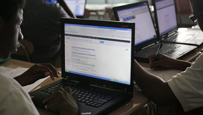 Students use computers for research during an AP government class at the Academy for College and Career Exploration in Baltimore.