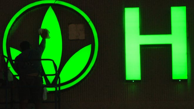 A worker cleans the logo on the Herbalife sign.