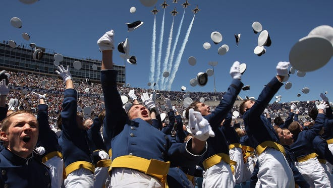 Air Force Academy graduates celebrate as a team of F-16 Thunderbirds flies over during  the U.S. Air Force Academy graduation ceremony at Falcon Stadium on May 27, 2009 in Colorado Springs, Colorado.