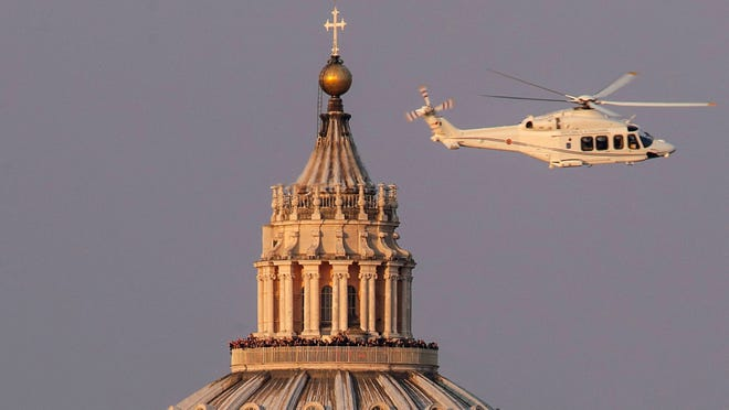 Image shows St Peter's Basilica with a helicopter carrying Pope Benedict XVI on Feb. 28.