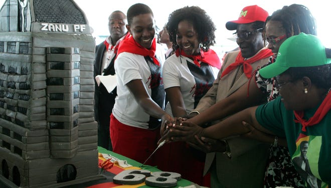 Zimbabwe's President Robert Mugabe (3rd R, with red cap) cuts his birthday cake with the first family, his children Chatunga Mugabe (2nd L) and Bona Mugabe (C) and his wife Grace Mugabe (2nd R) during a rally held in honor of his 89th birthday at Chipadze Stadium in Bindura on Saturday.