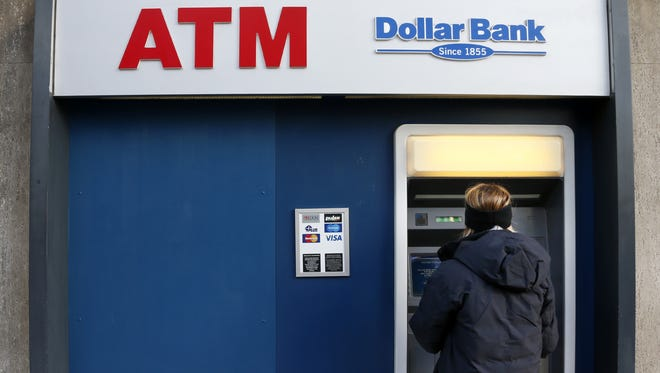 In this Jan. 5, 2013 photo, a woman uses an ATM machine in downtown Pittsburgh. U.S. consumers increased spending modestly in January but cut back on major purchases that signal confidence in the economy. (AP Photo/Gene J. Puskar) ORG XMIT: NYBZ186