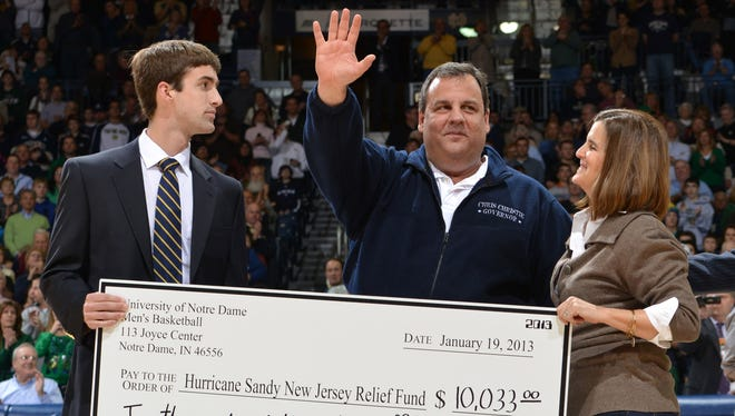 New Jersey Gov. Chris Christie waves to the crowd after accepting a check for Hurricane Sandy relief on Jan. 19, 2013 in South Bend, Ind. The check was presented during a timeout in basketball game between Rutgers and Notre Dame.