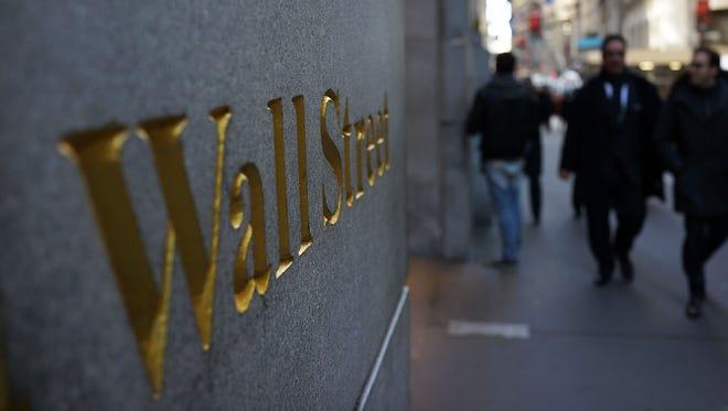People walk along Wall Street near the New York Stock Exchange.