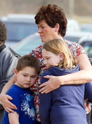 An unidentified woman and her children visit the crash site that claimed the lives of six teens early in the morning on Park Ave. in Warren, Ohio on Sunday.