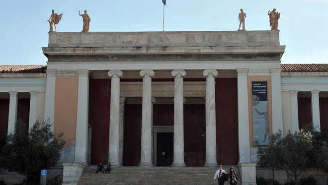 Tourists walk away from the closed archaeological museum in Athens during a 24-hour strike by culture ministry employees on Monday. The building is among 28 that the government is attempting to sell.