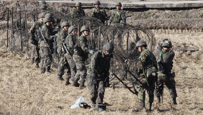 South Korean soldiers set up barbed wire fence during an exercise against possible attacks by North Korea near the border village of Panmunjom in Paju, South Korea, on March 11. South Korea and the United States are holding an annual military drill amid worries about possible bloodshed after North Korea's threat to scrap a decades-old war armistice.
