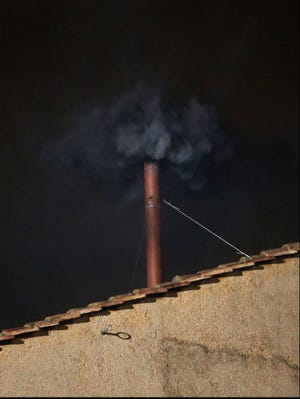 Black smoke billows out from a chimney on the roof of the Sistine Chapel.