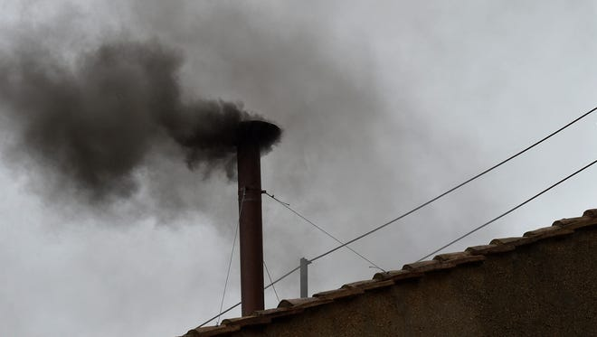 Black smoke rises from the chimney on the roof of the Sistine Chapel on Wednesday.