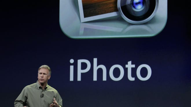 Apple Phil Schiller talks about the new iPad with iPhoto during an Apple announcement in San Francisco, Wednesday, March 7, 2012.