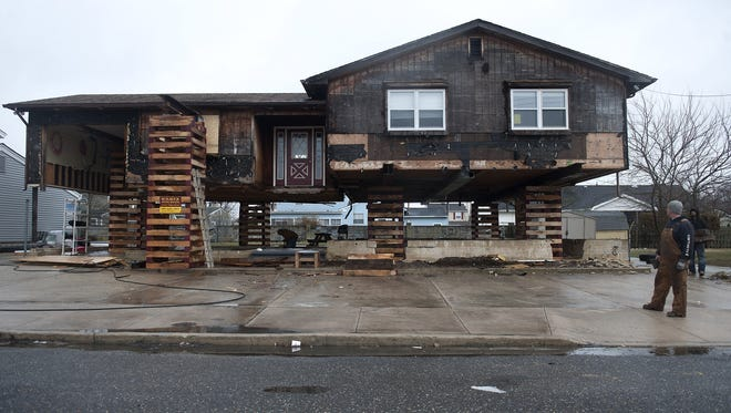 Steven Hauck, owner of SJ Hauck House Movers, looks March 8 at one of the many homes his company is elevating in Brigantine, N.J. The home is being raised 7.5 feet above its original foundation to comply with new flood insurance rules in wake of Hurricane Sandy.