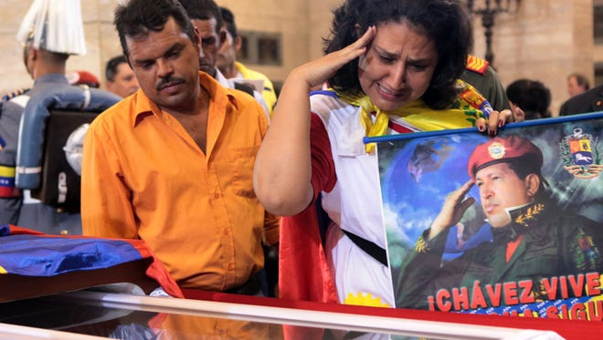 Supporters of President Hugo Chavez pay their last respects to their leader during his funeral at the Military Academy in Caracas, Venezuela, on March 10
