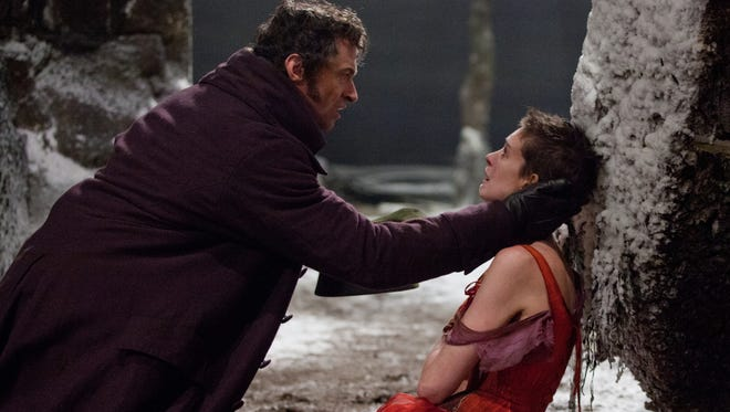 "This film image released by Universal Pictures shows Hugh Jackman as Jean Valjean, left, and Anne Hathaway as Fantine in a scene from ""Les Miserables."""
