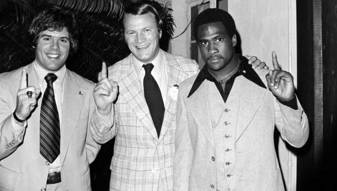 Steve Davis, left, stands with Oklahoma coach Barry Switzer and running back Joe Washington after after the Sooners beat Michigan in the 1976 Orange Bowl to win a national title.