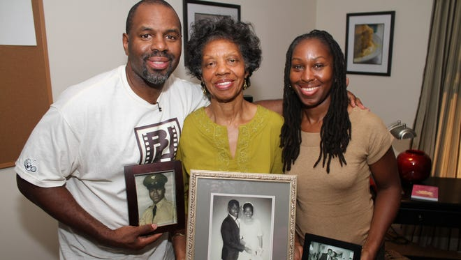 """""""Soul Food Junkies"""" filmmaker Byron Hurt with his mother, Frances, and sister Taundra display photographs of Jackie Hurt. Byron pays homage to his father, Jackie, who died of pancreatic cancer. Byron believes soul food contributed to his father's death in 2007. Now he is on a mission to educate people about the dangers of high-fat diets through his documentary film."""