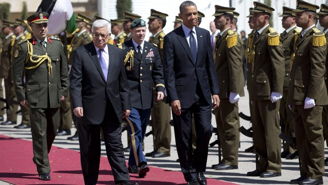 President Obama, right, and Palestinian President Mahmoud Abbas walk a red carpet for a troop review during an arrival ceremony at the Muqata Presidential Compound on March 21 in the West Bank town of Ramallah.