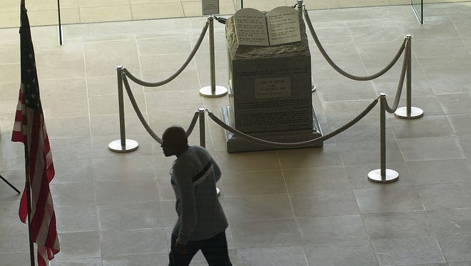 A man walks past the Ten Commandments monument in the rotunda of the Alabama Judicial Building on Nov. 18, 2002. A federal judge ordered the monument removed.