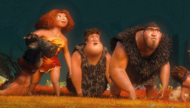 Eep (Emma Stone), left, Thunk (Clark Duke) and Grug (Nicolas Cage) explore an unknown world in 'The Croods.'